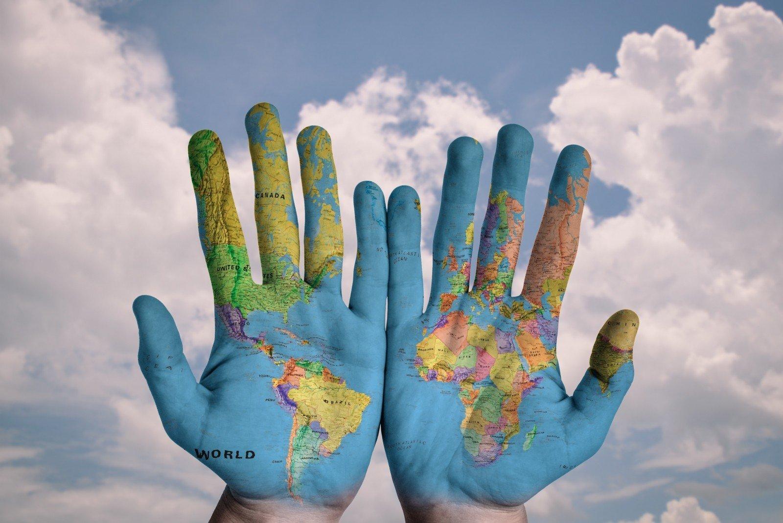 peinture de la map monde sur les deux mains d'une personne